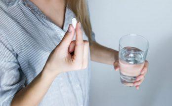 Frau mit Glas Wasser und Tablette / Medikament
