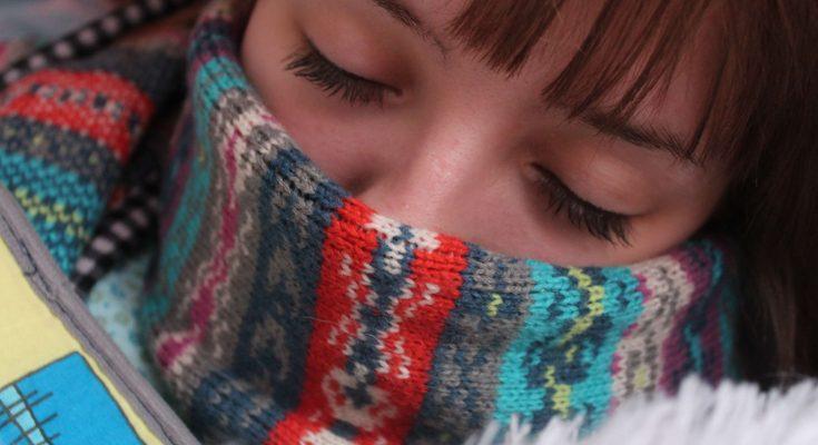 Frau mit Grippe und Schal